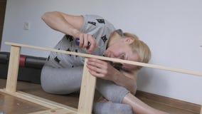 Una donna che si siede sul pavimento raccoglie la mobilia di legno nella stanza, torce le viti con un cacciavite stock footage
