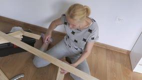 Una donna che si siede sul pavimento raccoglie la mobilia di legno nella stanza, torce le viti con un cacciavite archivi video