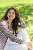 Una donna che si siede sull'erba Immagine Stock