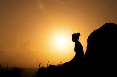 Una donna che si siede sulla collina Fotografia Stock