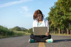 Una donna che si siede sulla strada e che per mezzo del computer portatile fotografie stock