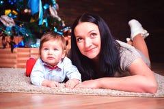Una donna che si trova sul pavimento nella stanza abbraccia delicatamente suo figlio immagini stock