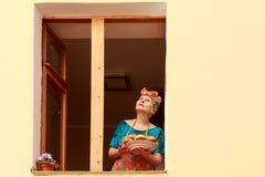 Una donna che sta alla finestra, sognante Immagini Stock