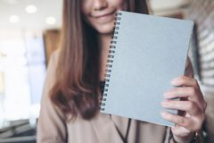 Una donna che tiene e che mostra il taccuino grigio in bianco di colore nell'ufficio Immagini Stock