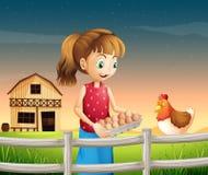 Una donna che tiene un eggtray con le uova vicino al recinto Immagine Stock