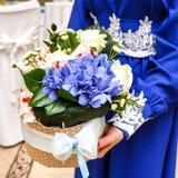 Una donna che tiene un mazzo dei fiori nel canestro del regalo Immagine Stock Libera da Diritti