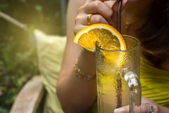 Una donna che tiene un vetro di limonata per la bevanda immagine stock libera da diritti