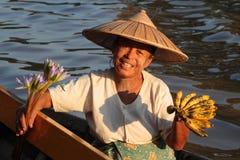 Una donna che vende frutti e fiore dalla sua piccola barca Fotografia Stock Libera da Diritti