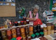 Una donna che vende gli inceppamenti, vino e miele nel mercato armeno immagini stock