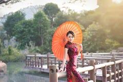 Una donna cinese classica vestita nel cheongsam Fotografie Stock