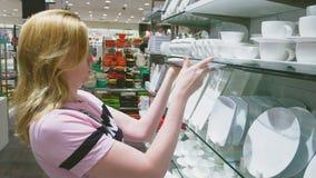 Una donna compra i piatti nel deposito, esamina i vari oggetti dei piatti video d archivio