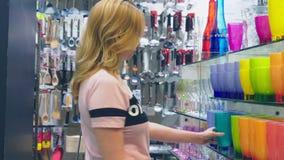 Una donna compra i piatti nel deposito, esamina i vari oggetti dei piatti stock footage