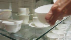 Una donna compra i piatti nel deposito, esamina i vari oggetti dei piatti archivi video