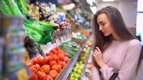 Una donna compra i pomodori in un supermercato video d archivio