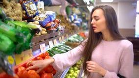 Una donna compra i pomodori in un supermercato archivi video