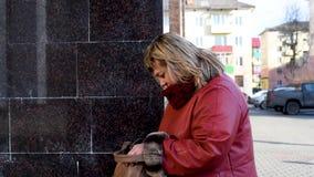 Una donna con capelli biondi in tuta sportiva fermata nella via che cerca un telefono nella sua borsa archivi video