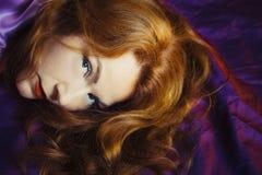 Una donna con capelli rossi e le labbra rosse che guardano direttamente nella macchina fotografica Fotografia Stock Libera da Diritti