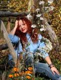 Una donna con capelli rossi si siede su erba verde e esamina la macchina fotografica immagini stock libere da diritti