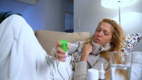 Una donna con febbre che si trova sullo spruzzo del sofà, di tosse e di usi per la gola carrello stock footage