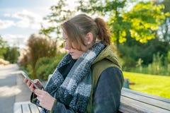 Una donna con il telefono cellulare sta redigendo un messaggio di testo fotografia stock libera da diritti