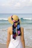 Una donna con il vestito ed il cappello sulla spiaggia Immagine Stock Libera da Diritti