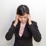 Una donna con l'emicrania, emicrania, sforzo, postumi di una sbornia nell'affare ex Immagini Stock Libere da Diritti