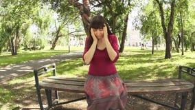 Una donna con la depressione e un'emicrania che si siede nel parco che segna whiskey stock footage