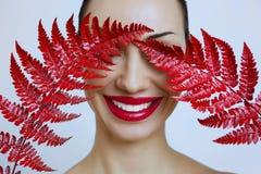 Una donna con le labbra rosse sensuali e una felce rivestono fotografia stock libera da diritti