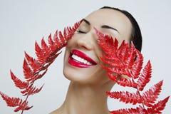 Una donna con le labbra rosse sensuali e una felce rivestono Rossetto rosso immagine stock