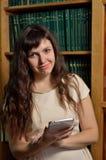 Una donna con un aggeggio contro il leggio Fotografie Stock Libere da Diritti
