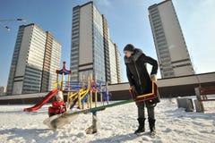 Una donna con un bambino in un'oscillazione in un giorno soleggiato di inverno Immagini Stock Libere da Diritti