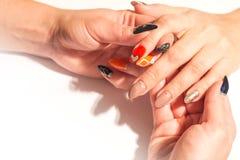 Una donna con un bello manicure tiene la mano di un'altra ragazza con un cuore dipinto sulla sua unghia fotografie stock libere da diritti