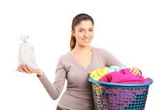 Una donna con un cestino di lavanderia che tiene un sacchetto dei soldi Immagini Stock