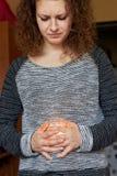 Una donna con un fronte torto tiene le sue mani sul suo stomaco, tramite cui i passaggi leggeri Mal di stomaco fotografia stock