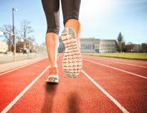 Una donna con un paio atletico delle gambe che vanno per un dur di funzionamento o di trotto fotografia stock