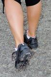 Una donna con un paio atletico delle gambe che vanno per un trotto immagine stock