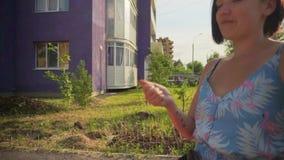 Una donna con un passeggiatore sui precedenti di una casa multipiana archivi video