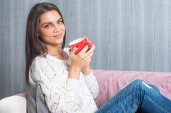 Una donna con una tazza rossa in sue mani, sedute sullo strato, sguardo di sorrisi del sofà alla macchina fotografica Fotografia Stock