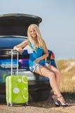 Una donna con una valigia vicino all'automobile Immagini Stock