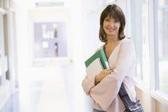 Una donna con uno zaino che si leva in piedi in un corridoio Fotografie Stock Libere da Diritti