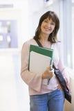 Una donna con uno zaino che si leva in piedi in un corridoio Fotografia Stock