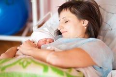Una donna cura un neonato Fotografia Stock