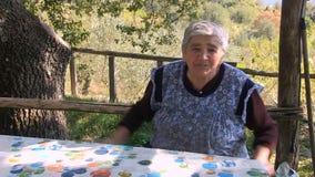 Una donna d'annata anziana che racconta una storia al paese MF video d archivio