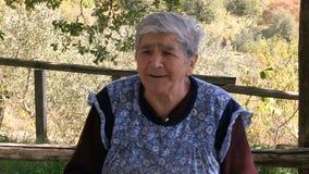 Una donna d'annata anziana che racconta una storia circa i suoi figli vicini sul MF archivi video