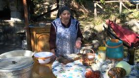 Una donna d'annata anziana che racconta una storia in un'azienda agricola MF video d archivio