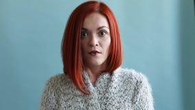 Una donna dai capelli rossi in un cardigan lungo molto è colpita archivi video