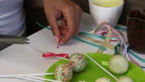 Una donna decora gli archi degli schiocchi del dolce della treccia che si trovano su un piatto video d archivio