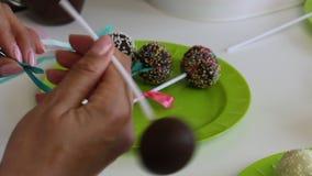 Una donna decora gli archi degli schiocchi del dolce della treccia che si trovano su un piatto Candy ha decorato con i colori dif video d archivio