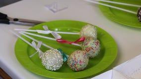 Una donna decora gli archi degli schiocchi del dolce della treccia che si trovano su un piatto Candy ha decorato con i colori dif archivi video