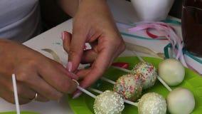 Una donna decora gli archi degli schiocchi del dolce della treccia che si trovano su un piatto Candy ha decorato con il condiment archivi video